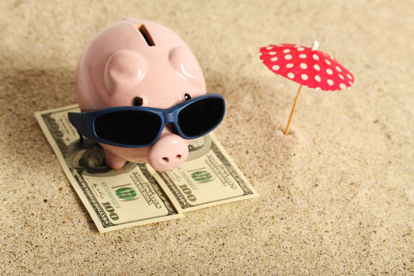 Summer-piggy-bank-standing-on-towel-from-greenback-hundred-dollars-with-sunglasses-on-the-beach-and-red-parasol